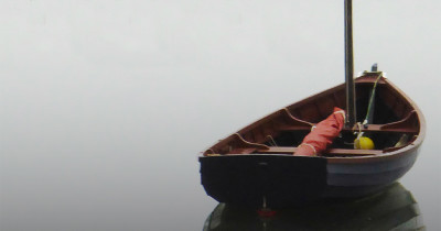 photo of row boat on calm water